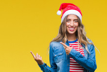 Beautiful Young Blonde Woman Wearing Christmas Hat Over Isolated Background Smiling And Looking At The Camera Pointing With Two Hands And Fingers To The Side.