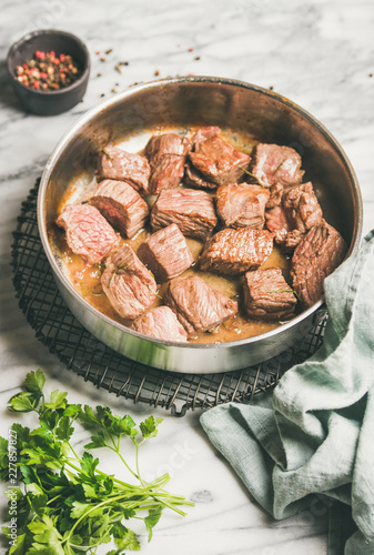 Meat dinner. Braised beef meat stew with fresh parsley in cooking pan over white marble table background. Comfort winter food