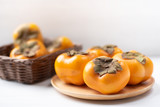 Ripe persimmon fruit on wooden plate and basket, healthy fruit