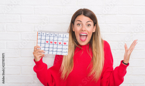 Fotografía Young adult woman over white brick wall holding period calendar very happy and e