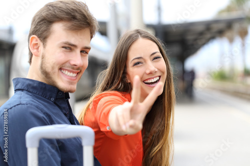 Couple of happy travelers posing in a train station