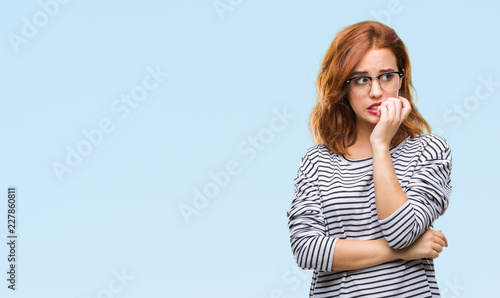 Fotografía Young beautiful woman over isolated background wearing glasses looking stressed and nervous with hands on mouth biting nails