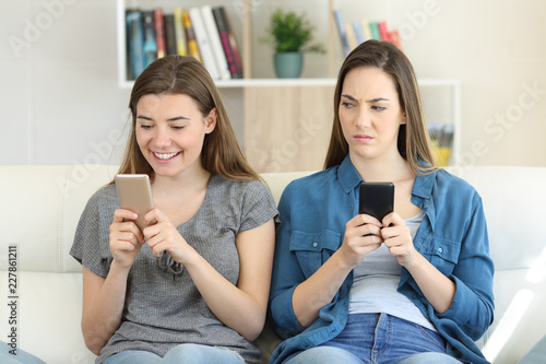Envious woman looking at her friend texting in a phone Fototapeta