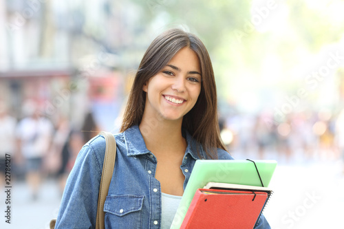 Happy student poses looking at camera in the street