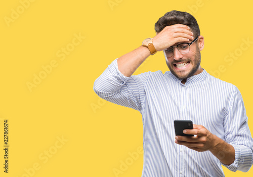 Fotografía  Young handsome man texting using smartphone over isolated background stressed with hand on head, shocked with shame and surprise face, angry and frustrated