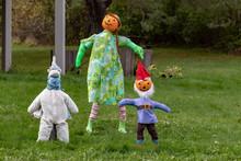 Boy And Girl Pumpkin Scarecrow In Autumn Park