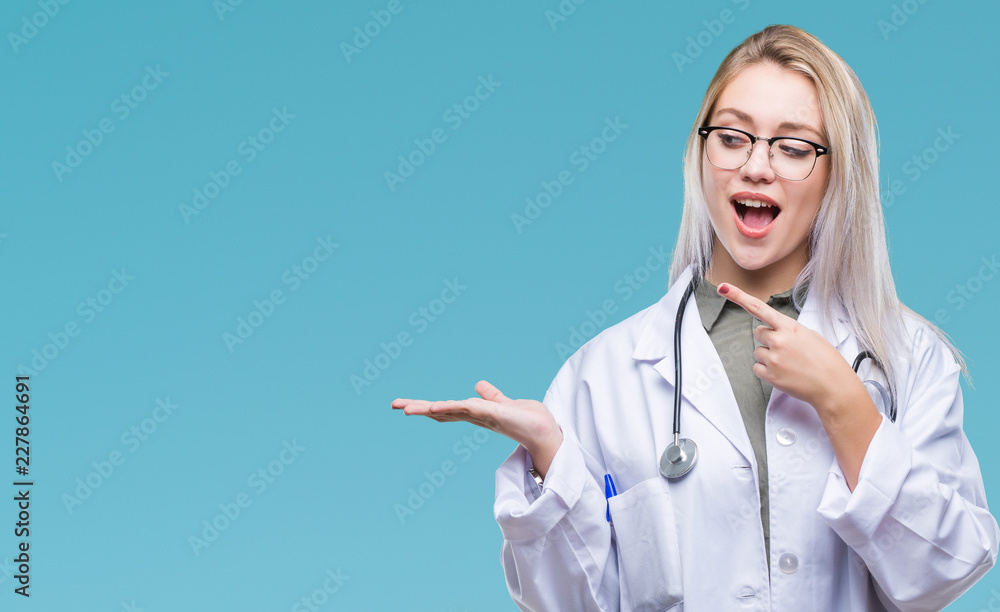 Fototapety, obrazy: Young blonde doctor woman over isolated background amazed and smiling to the camera while presenting with hand and pointing with finger.