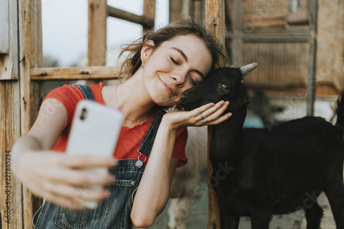 Happy girl taking a selfie with a black baby goat Poster Mural XXL