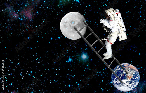 the cosmonaut on ladder traveling on moon.elements of this image furnished by NASA