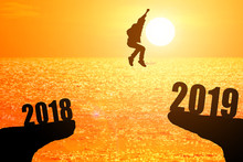 Silhouette Of Young Man Jumping Between 2018 And 2019 Years With Beautiful Sunset At The Sea-concepts Of News Year And Business Target.
