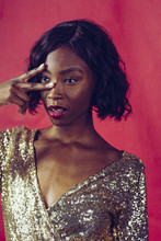 Portrait Of A Beautiful Woman With Fingers In Front Of Her Face In Golden Sequin Dress