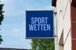Ein Schild an der Hauswand weist auf Sport Wetten Annahme hin