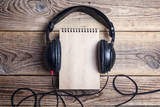 Blank notebook with a headphones on it on wooden background.