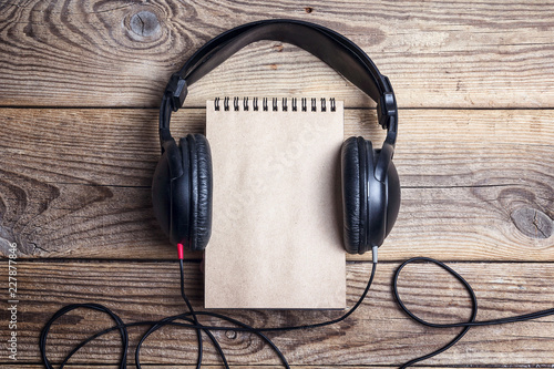 Blank notebook with a headphones on it on wooden background. - 227877846