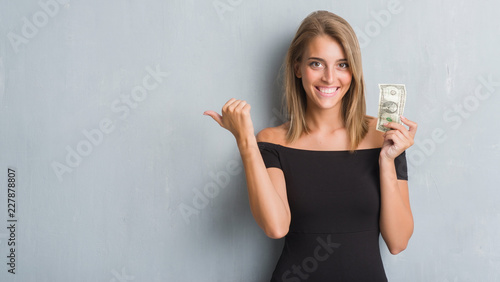 Fotografía  Beautiful young woman over grunge grey wall holding a dollar pointing and showin