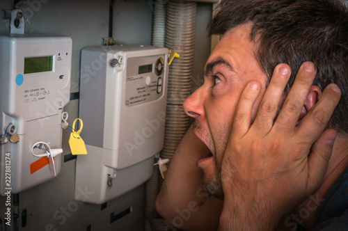 Man is checking electricity meter - expensive electricity concep
