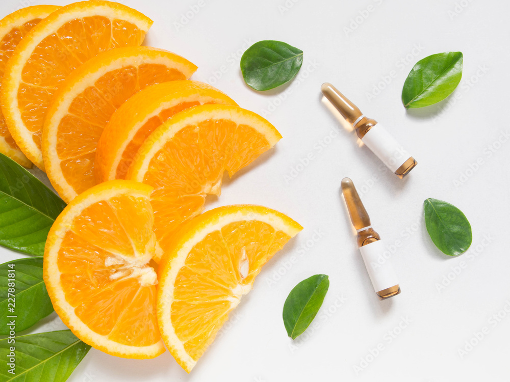 Fototapeta Top view of vitamin C brown ampule for injection with fresh juicy orange fruit slides and green leaves on white table. Vitamin synthetic or natural nutrition choices concept. Beauty product mock-up.