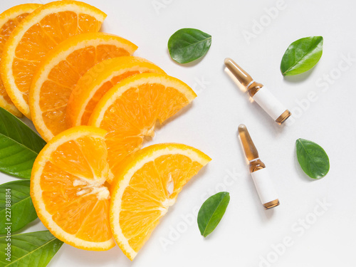 Fototapeta Top view of vitamin C brown ampule for injection with fresh juicy orange fruit slides and green leaves on white table. Vitamin synthetic or natural nutrition choices concept. Beauty product mock-up. obraz