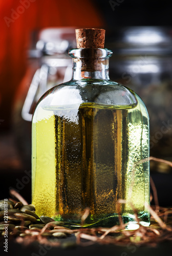 In de dag Aromatische Healing pumpkin seed oil in glass bottle, dark table, selective focus