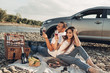 Happy Traveler Couple on Picnic into the Sunset with SUV Car
