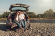 Happy Couple on Roadtrip into the Sunset in SUV Car