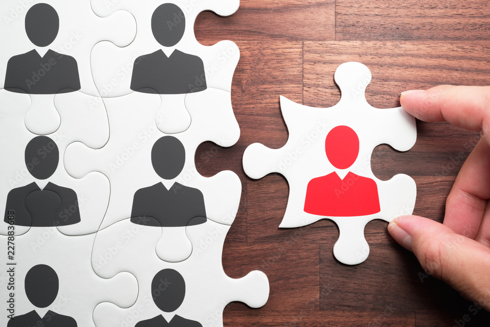 Fototapeta Human resource management. Personnel, employment and recruitment concept.Selecting person for the job. Assembling jigsaw puzzle on wood desk.