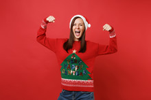 Cheerful Strong Young Santa Girl In Sweater, Christmas Hat Screaming Showing Biceps, Muscles Isolated On Red Wall Background. Happy New Year 2019 Celebration Holiday Party Concept. Mock Up Copy Space.