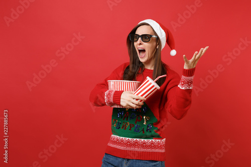 Photo Scared young Santa girl in 3d imax glasses watching movie film, hold popcorn, cup of soda spread hands screaming isolated on red wall background