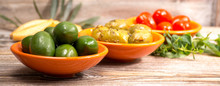 Tapas Or Italian Appetizer, Green Olives And Cherry Tomatoes Served In Small Orange Bowls