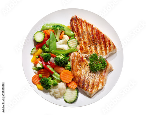plate of grilled chicken with vegetables on wite background, top view