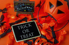 Halloween Background - Trick Or Treat On Black Wooden Tag With Pumpkin Bag And Black And Orange Candies On Orange Background