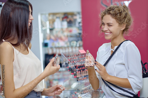 Obraz View from side of two ladies talking together in shop - fototapety do salonu