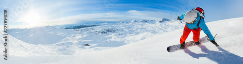Snowboarder skiing downhill, panoramic format