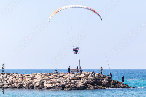The athlete on a colored motorized parachute flies during the day.city embankment of the Mediterranean in the Nahariyya city in Israel