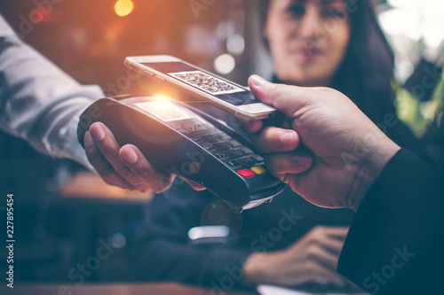 Valokuva  Young man hands are Smartphone to scan a QR CODE filing from a credit card reader to pay for food and beverages in restaurants which have a romantic atmosphere by the Asian girls are sitting together