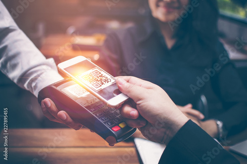 Fotografía Young man hands are Smartphone to scan a QR CODE filing from a credit card reader to pay for food and beverages in restaurants which have a romantic atmosphere by the Asian girls are sitting together