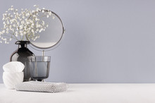 Modern Elegant Female Dressing Table With Black Glass Vase With Flowers, Mirror, Silver Cosmetic Bag On Grey Color Wall And White Wood Board.