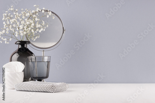 Modern elegant female dressing table with black glass vase with flowers, mirror, silver cosmetic bag on grey color wall and white wood board Fototapet