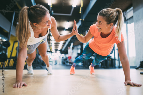 Poster Fitness Two sporty girls doing push ups in gym