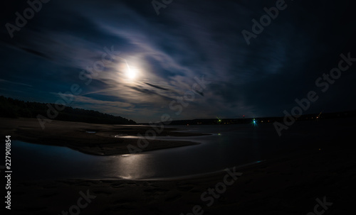A long exposure shot of Tom river with moonlit water and shores under the cloudy night sky, foot-marks on sand Canvas-taulu