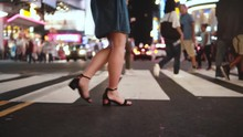 Slow Motion Lifestyle Shot Of Beautiful Young Female Legs Walking Across Crowded Street At Night In Times Square, NY.