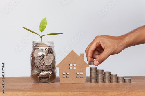 Fotografía  Hand putting money coins to row of coins and house model with plant growing on coins in glass jar on wooden table