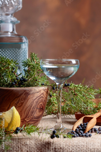 Blue gin, lemon and a branch of juniper with berries.