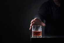 Man's Hand Reaches For A Glass Of Alcohol.