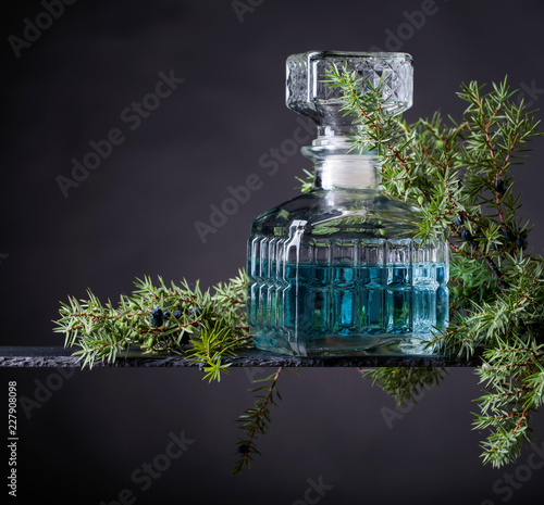 Blue gin in crystal decanter and juniper branch with berries .