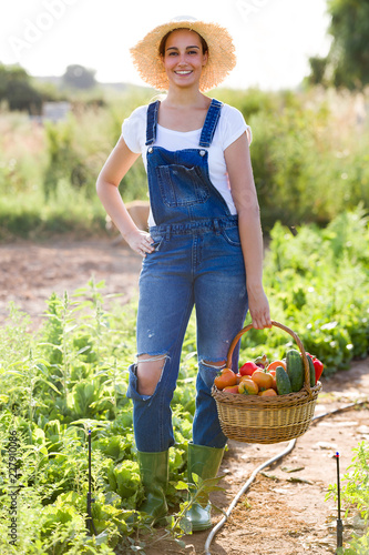 Beautiful young smiling woman holding basket with fresh vegetables from the garden looking at the camera.