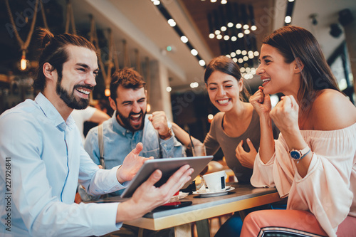 Group of Happy friends having with digital tablet in cafe