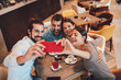 canvas print picture Group of Happy friends having making selfie in cafe