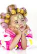 Девочка в банном розовом халате с бигудями и кусочками огурцов на лице.