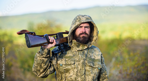 Foto op Canvas Jacht Bearded hunter rifle nature background. Hunting big game typically requires tag each animal harvested. Experience and practice lends success hunting. Hunting season. Guy hunting nature environment